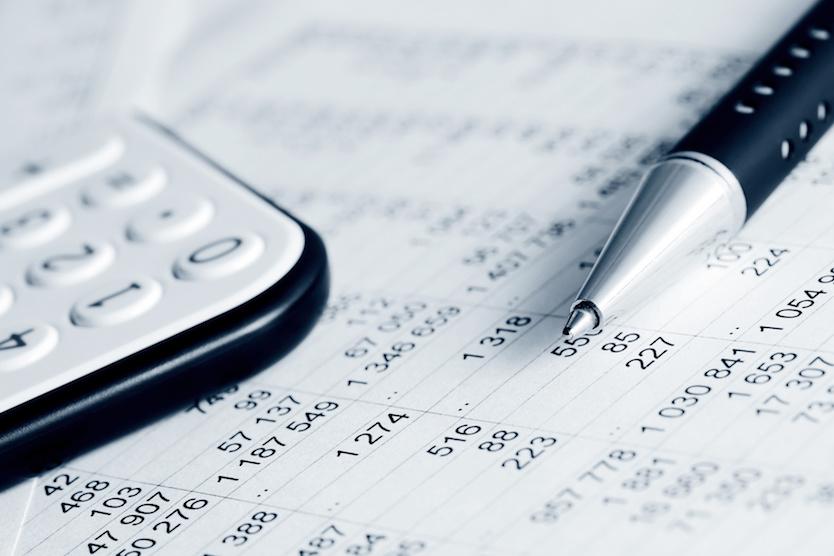 Stift, Taschenrechner und Tabelle mit Zahlen