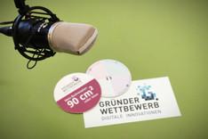Dieses Bild zeigt ein Studiomikrofon und Print-Materialien des Gründerwettbewerbs.