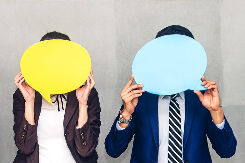 Menschen halten Sprechblasen vor ihr Gesicht