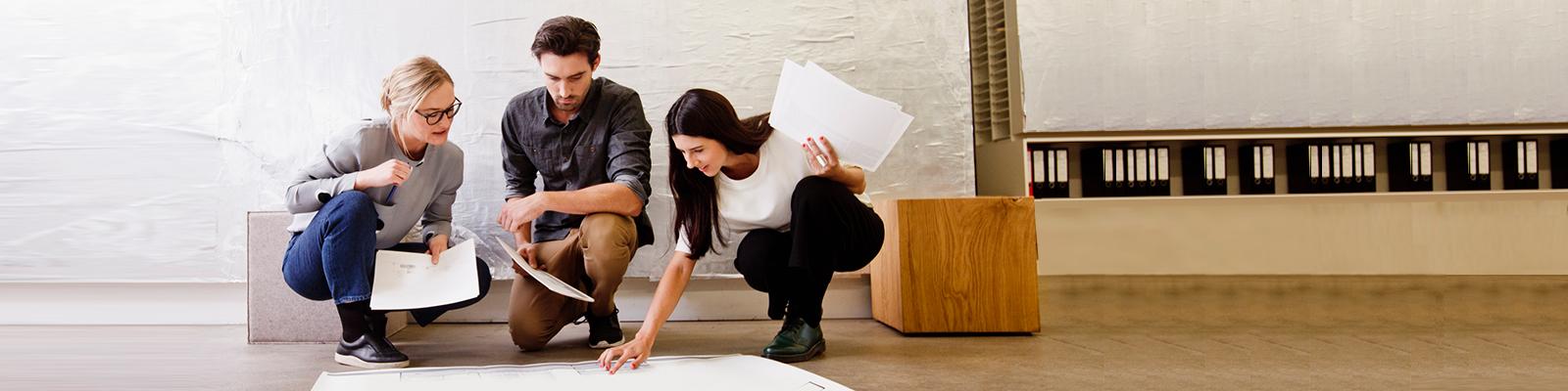 Junge Gründerinnen und Gründer sprechen über eine Zeichnung; Thema Existenzgründung; Quelle: Getty Images/Emely
